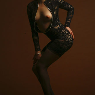 Molly with her dress unzipped showing her breasts, ntEscort in Surrey, Girlfriend Experience, Massage Parlour in Surrey