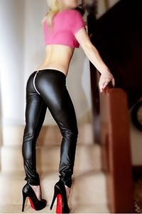 Young escort in tight rear zip latex trousers