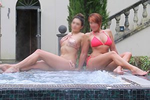 Two bikini clad escorts enjoying jacuzzi