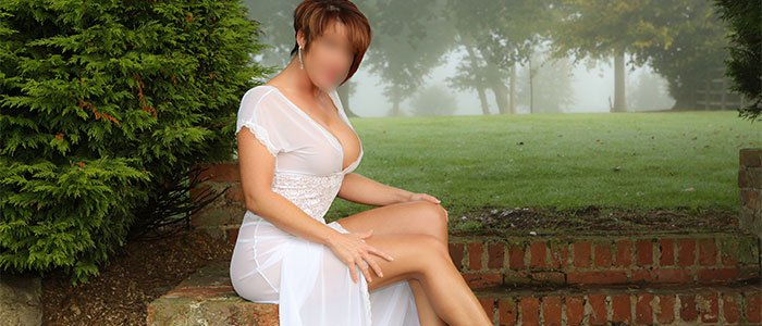 Lucy in white sitting on wall, high class English redhead