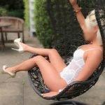Carmen posing outside, swing chair